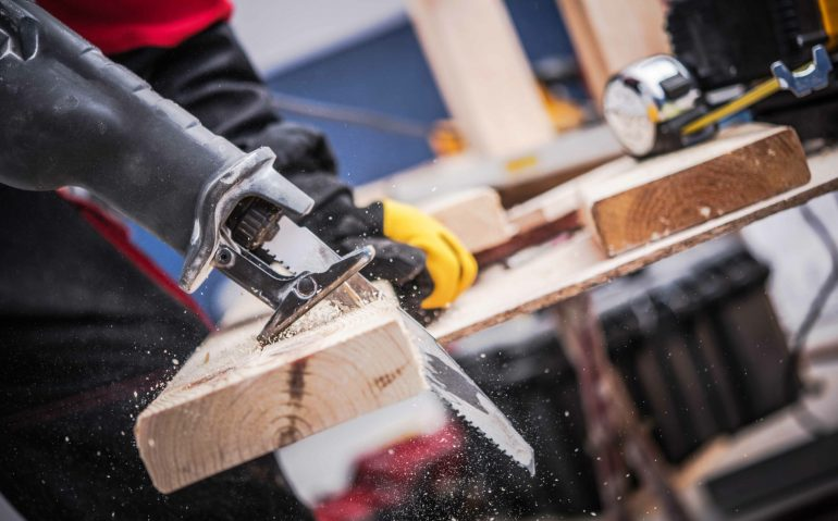 Small Construction Project. Men Cutting Piece of Wood Board Using Reciprocating Saw. Construction Site Power Equipment.